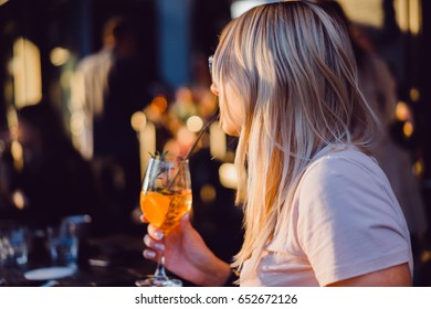 Blonde girl drinks a cocktail on a summer terrace in a street cafe in a European city.