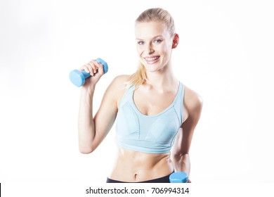 Blonde girl with dumbbell. Sporty lifestyle.