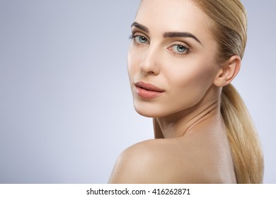 Blonde girl with fixed hair, blue big eyes, thick eyebrows and naked shoulders looking at camera at gray studio background, beauty photo, make up model, portrait.