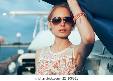 Blonde girl in flower dress and sunglasses holding  boat sails at sunset. Outdoor lifestyle portrait of woman