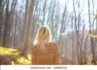 Blonde girl in the forest. Young Woman standing alone outdoor with wild forest mountains on background Travel Lifestyle. Concept  view. Girl in the forest.silhouette girl in the forest
