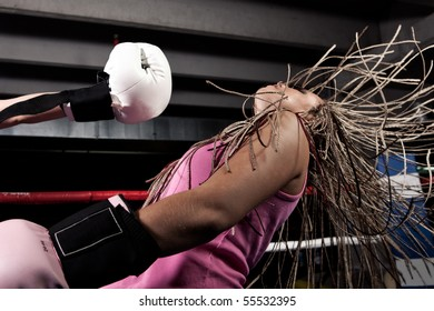 Blonde girl getting knocked out in a boxing ring