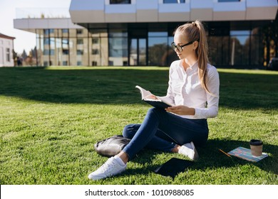 Blonde girl in glasses sits on the lawn and works with books