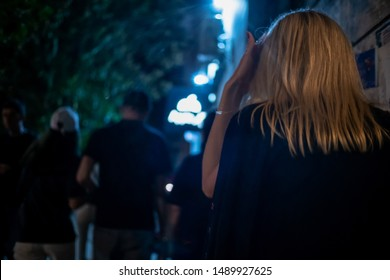 Blonde girl goes in crowd at night with her back to camera close up