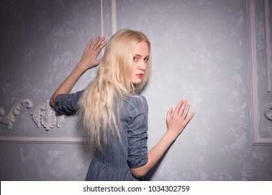 Blonde girl in a gray dress standing with her back and holds hands over vintage gray wall