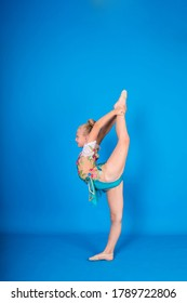 a blonde girl gymnast stands sideways in a gymnastic stance on a blue isolated background with space for text