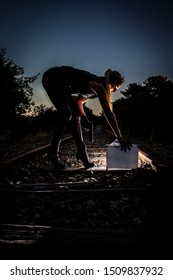 Blonde girl in handcuffs with suitcase on the background of an abandoned railway. Sexy woman in black leather clothes with gun at night. Criminal gangsta woman escape from mafia. Spy with weapon.