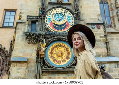 Blonde girl with hat and backback near famous clock in Prague, Czech Republic