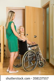 Blonde girl helping handicapped elderly woman to enter the apartment