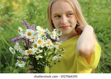 A blonde girl holding a bouquet of daisies in her hands on the background of nature.