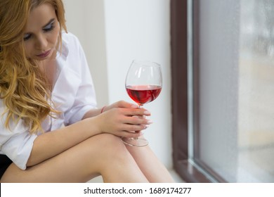 the blonde girl is holding the collar of her shirt smiling and holding red wine