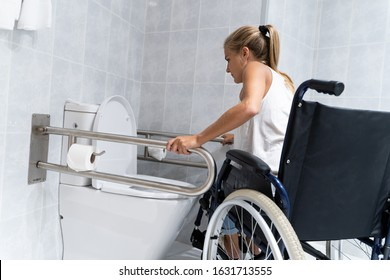 Blonde girl holding on to rails at the toilet trying to get up with her arms from a wheelchair to go to the bathroom