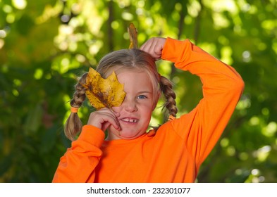Blonde girl holding two leaves with silly expression