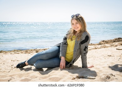Blonde girl in jeans sits on the seashore