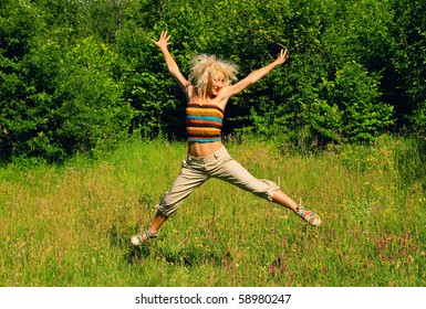 Blonde girl jumping on a green meadow