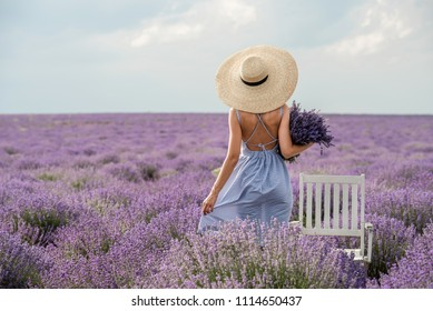 Blonde girl in lavender fields in Provence with a bouquet and in a hat