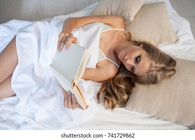 blonde girl lies in bed and reading a book at bedtime