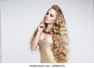 Blonde girl with long , shiny wavy hair . Beautiful model with curly hairstyle . Woman with beautiful hands french manicure