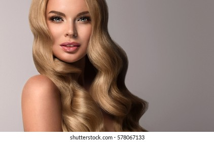Blonde  girl with long  and  volume shiny wavy hair .  Beautiful  woman model with curly hairstyle .