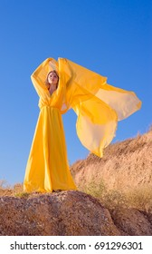 A blonde girl in a long yellow dress on a seashore