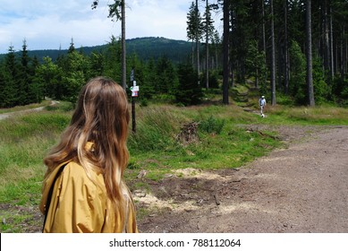 Blonde girl looking at man walking her side on mountain trail. Path leading to the top seen in the distance. Yellow jacket, sporty outfits. Green forest in the mountains. People hiking recreation.