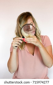 blonde girl looking at split ends with magnifying glass