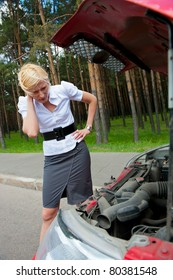 Blonde girl looks under the hood of a broken car