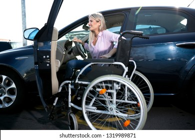 Blonde girl with loss of leg function sitting in the car on the parking space for disabled people