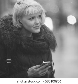 Blonde Girl with mobile street city black and white portrait.