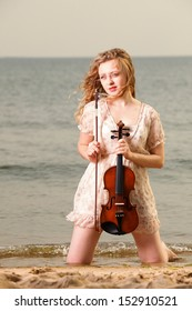 The blonde girl music lover on beach with a violin. Love of music concept.