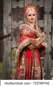A blonde girl in the national Russian red dress, shawl with fur and headdress kokoshnik standing near a wooden lattice wall of the ancient gate and smiling.Russian national clothes. Early spring time.
