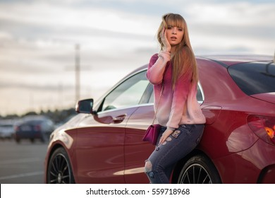 blonde girl near the red car