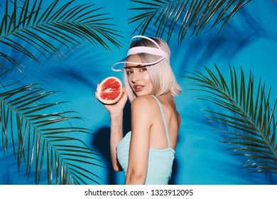 Blonde girl with nude make up wearing blue swimwear and cap posing at studio background with palms, holding fruit at blue background.