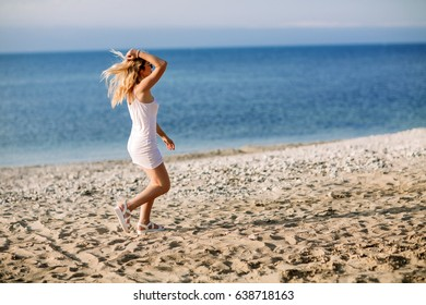 Blonde girl on the beach of the sandy beach by the sea.