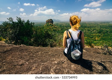 Blonde girl on a mountain overlooking nature and Sigiriya rock