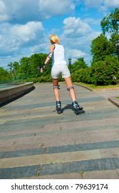 Blonde girl on roller skates rides in the park