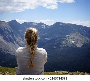 Blonde girl overlooking the Rocky Mountains