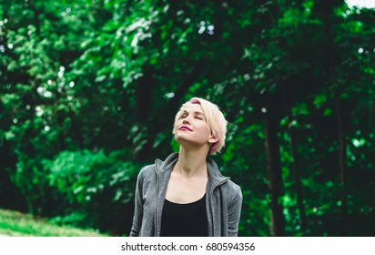 Blonde girl in the park with eyes closed