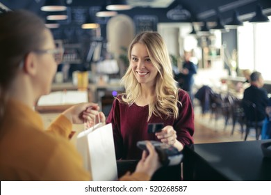 Blonde girl paying in a restaurant