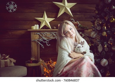 blonde girl in a photo studio with a fireplace and a Christmas tree