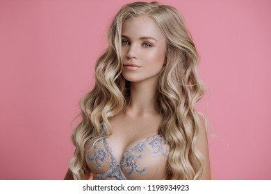 blonde girl posing in lingerie on pink background