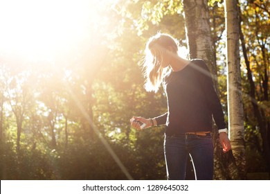 Blonde girl posing for photo in the park at sunset