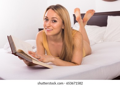 Blonde girl reading book on bed