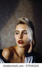 blonde girl with red lips in rock style. woman one shoulder bared. short hair