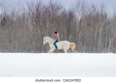 blonde girl riding horse bareback. Winter scene with snow.