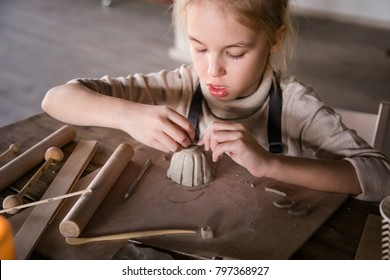 Blonde girl sculpts from clay with interest