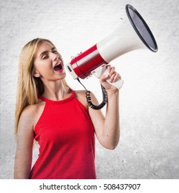 Blonde girl shouting by megaphone on textured background
