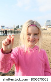 blonde girl shows her missing tooth which has fell out, missing here two front teeth