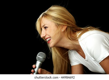 Blonde girl singing in microphone, isolated on black