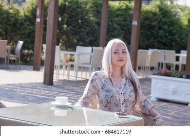 blonde girl sitting at the beach restaurant coffee